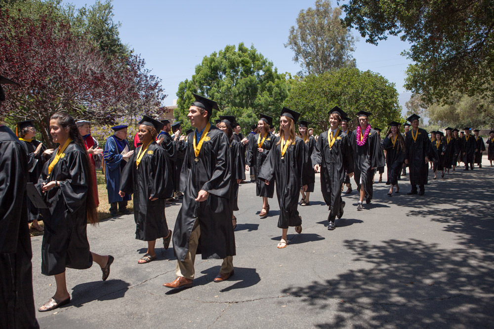 grads in caps and gowns walking