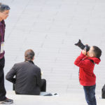 Young boy takes photo of parent at Harvey Mudd event