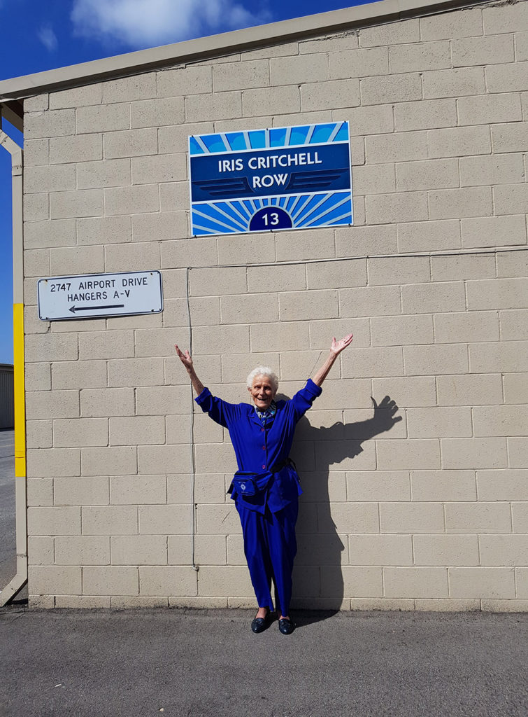 Iris Critchell in front of the hangar row that has been named for her