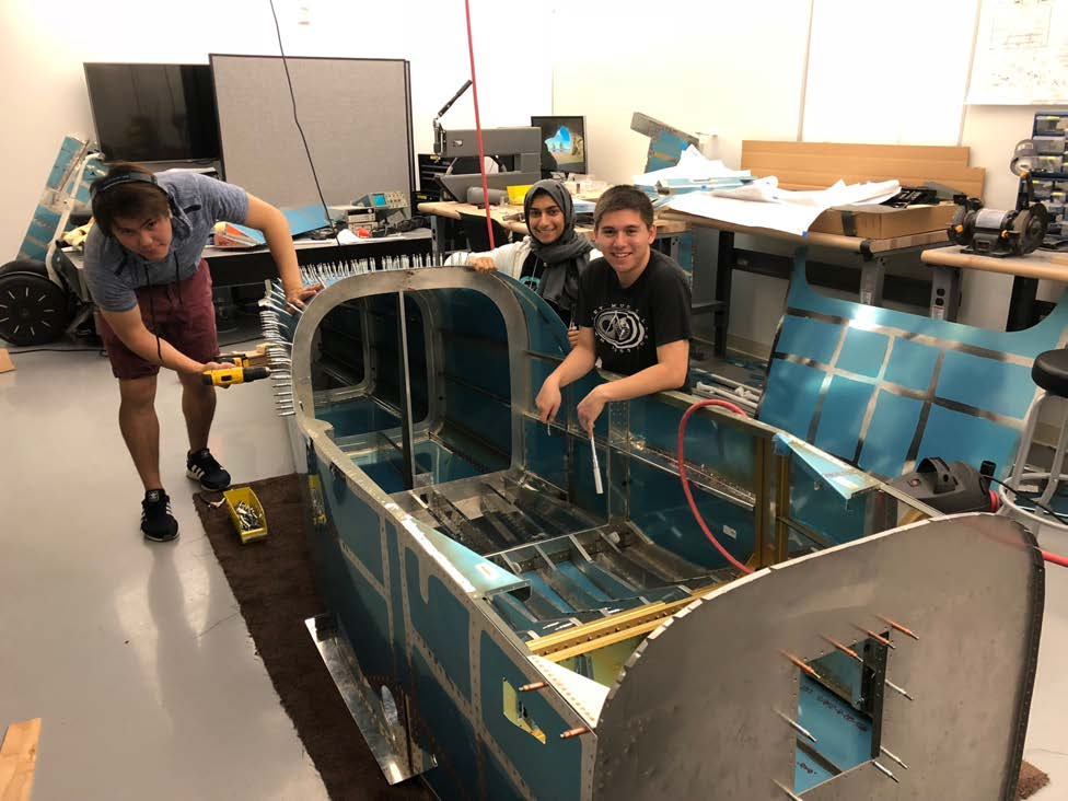 Students working on the body of an airplane