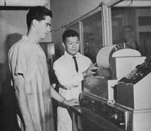 Barton Denechaud and Mits Kubota use lab equipment.