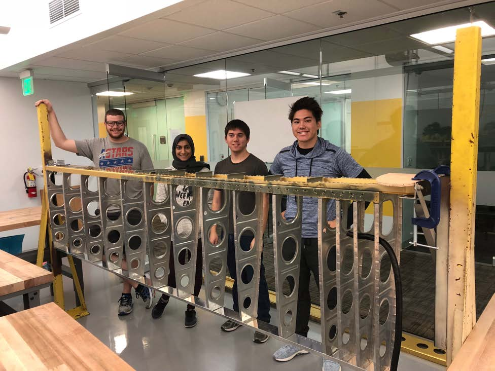student interns with airplane wing skeleton in lab