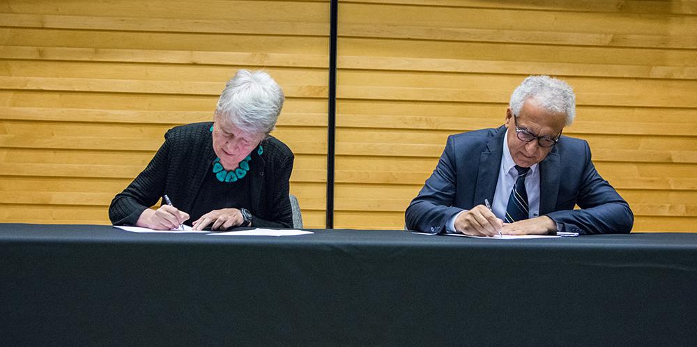 Maria Klawe signing paper