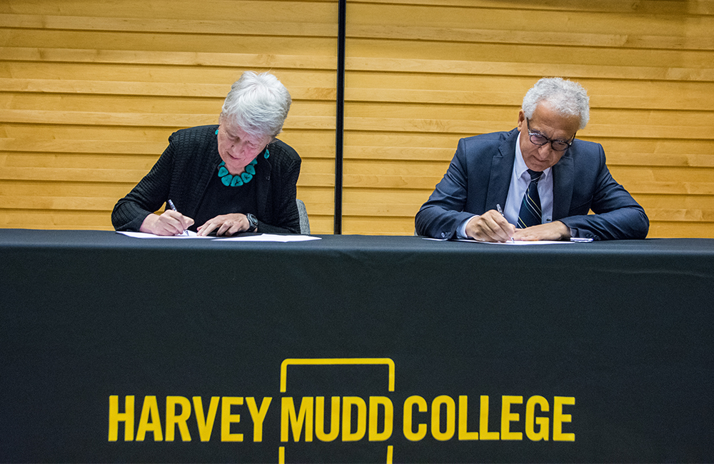 Man and woman sit at table signing documents