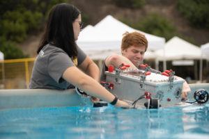 students putting AUV into water