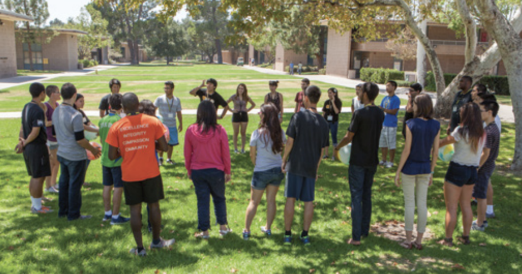 Summer Institute students form a circle outside on campus