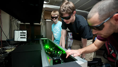 Students work on laser equipment.