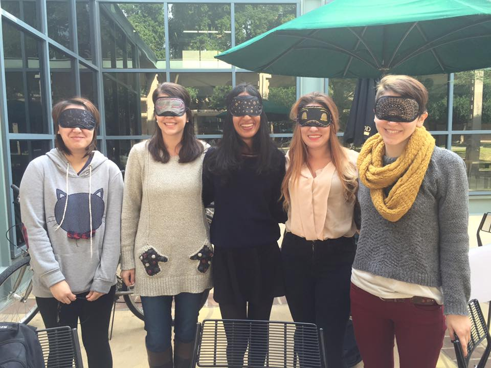 Wellness Peers and Michelle Harrison, Wellness Coordinator, pose with personalized sleep masks at their event outside of the Hoch.