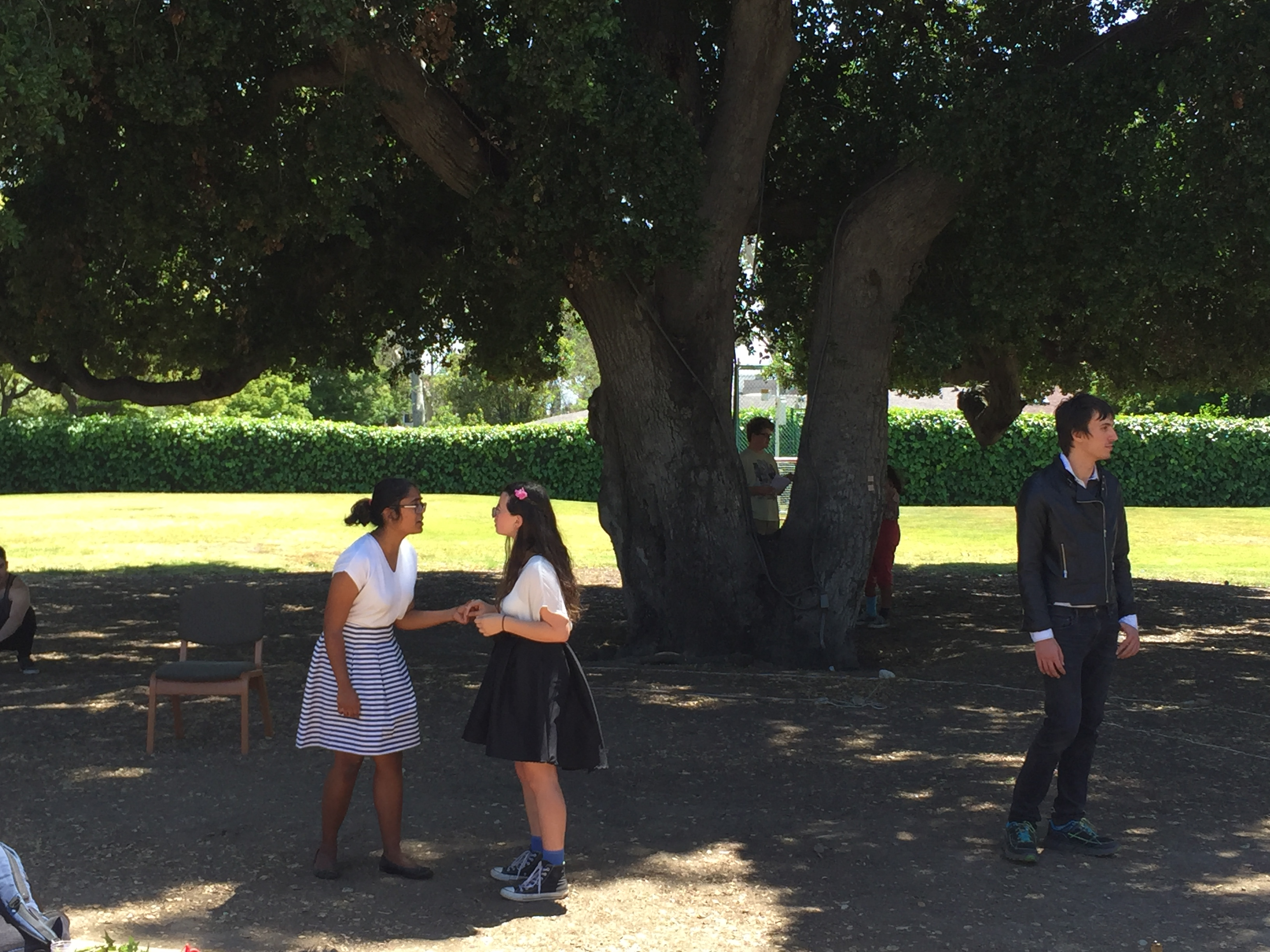Hermia and Helena speak to each other while Lysander stands off to the side