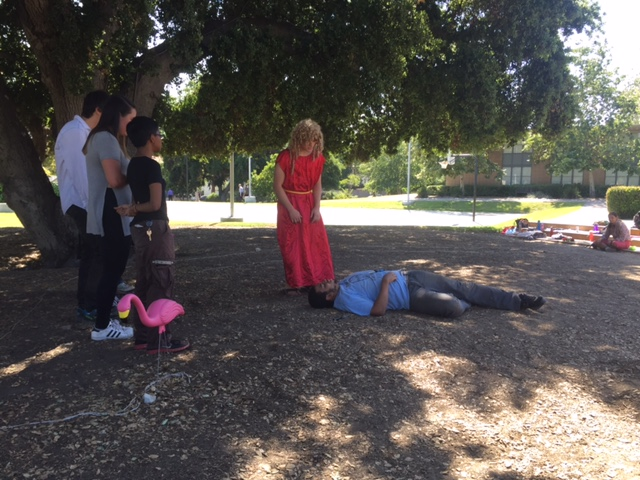 An actor lies on the ground while another stands over him.