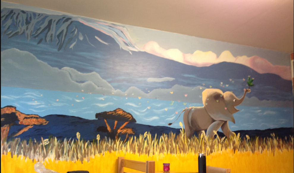 A mural of an elephant running through the grassland