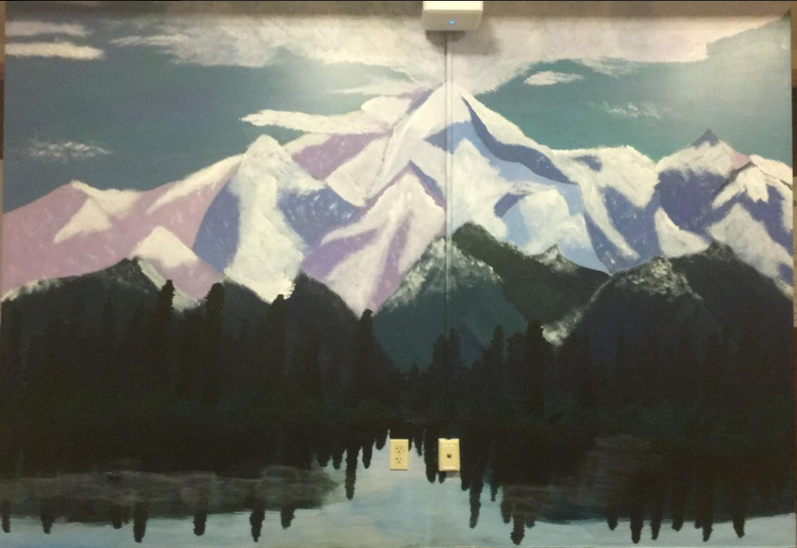 A mural of a forest with snowy purple peaks rising above