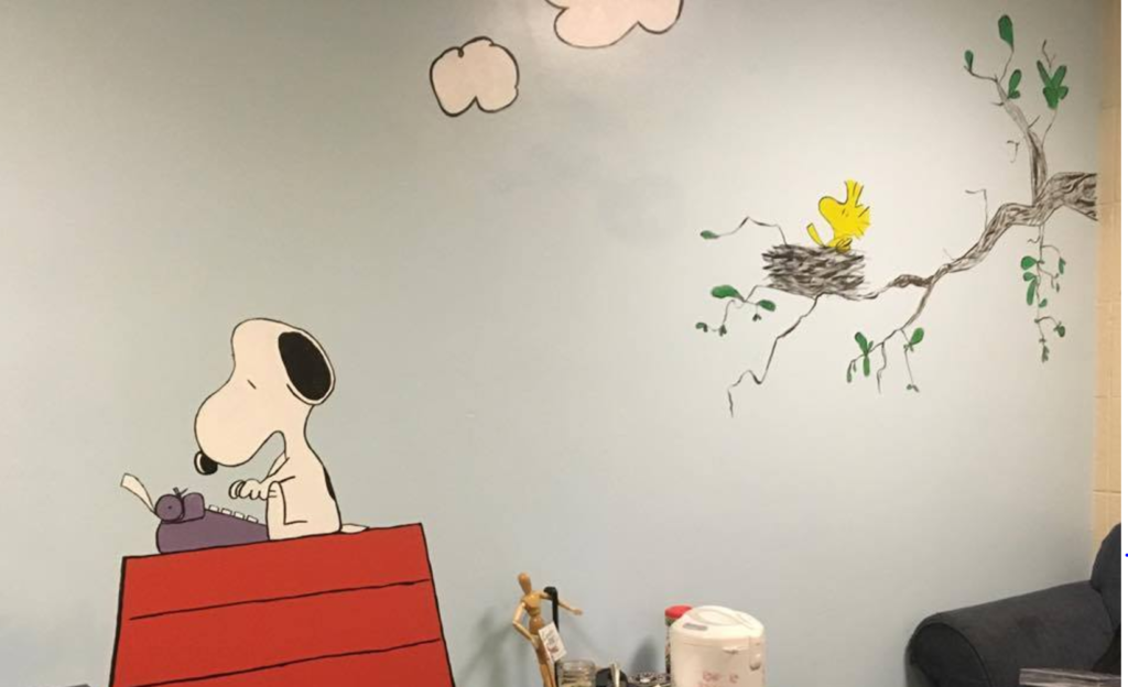 A mural of Snoopy typing on his red doghouse