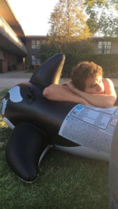 A student with his elbows propped up on an inflatable whale