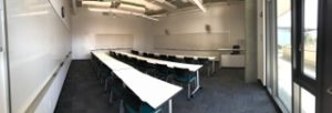 A panorama of a classroom, with white boards and rows of tables and chairs