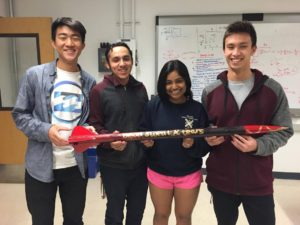 Four students hold a small rocket
