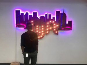 Kofi poses in front of the Lyft sign at their headquarters in San Francisco