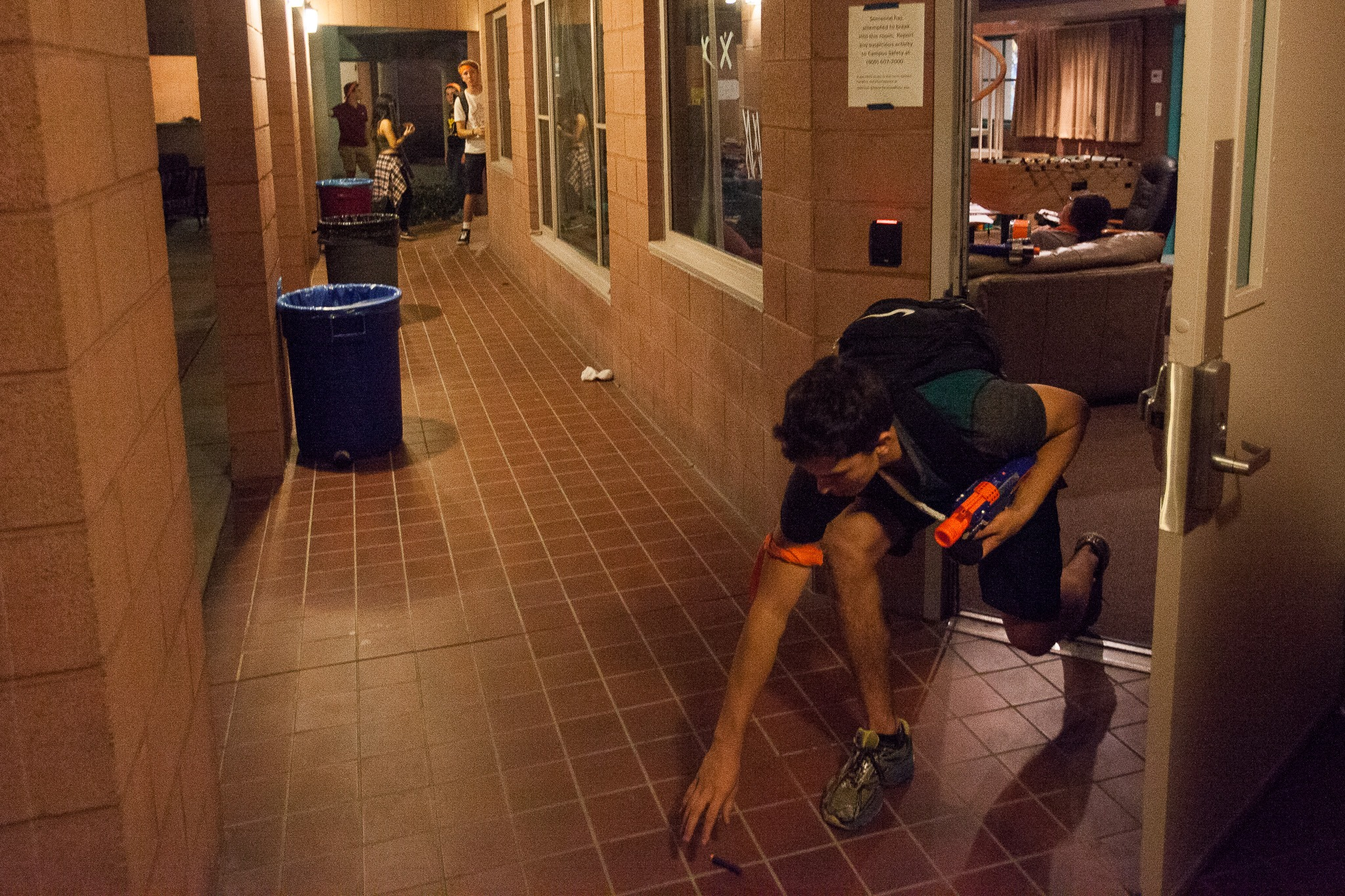 A student creeps out of a doorway during a stakeout in Case dorm. Photo credit: Liam Brooks
