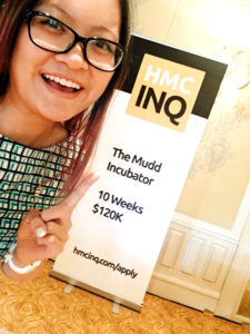 "Jeni points to the ""HMC INQ: The Mudd Incubator"" sign in front of a conference room"