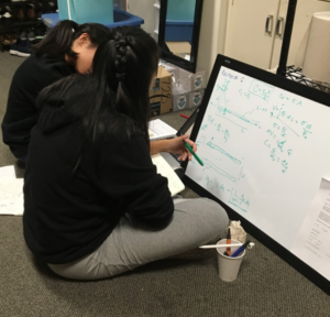 Two students sitting in front of a small whiteboard covered in diagrams and equations
