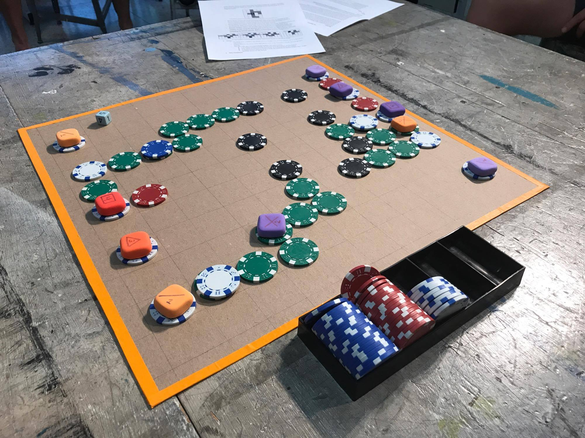 Poker chips and colorful rubber pieces on a brown wood board.