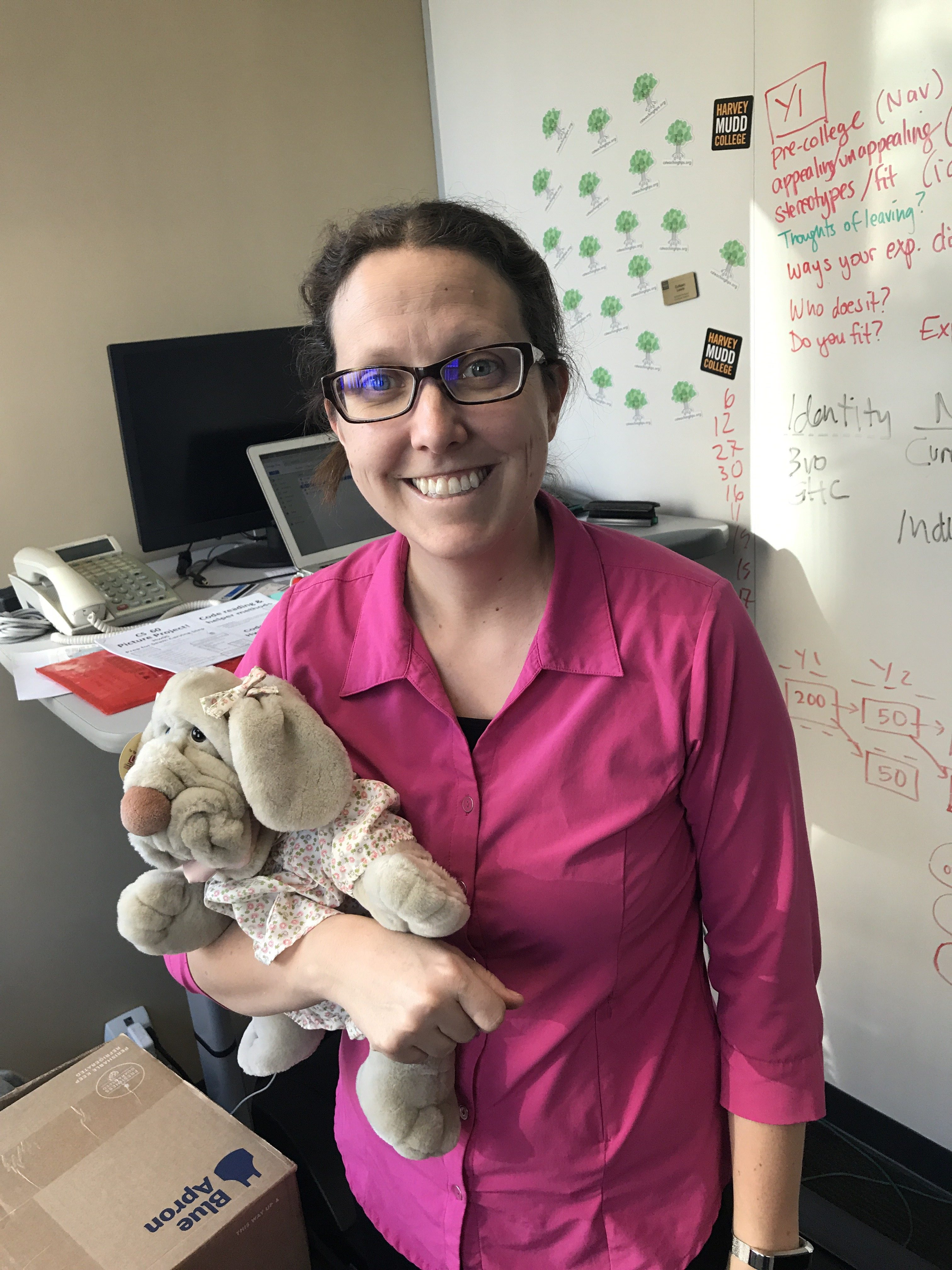 Professor Colleen Lewis holding a stuffed dog in her office