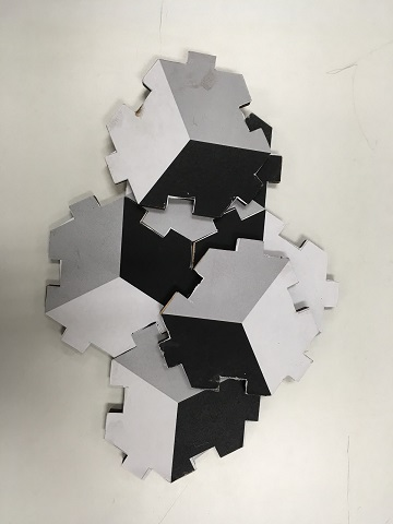 Black, white, and gray Hexmound pieces, with notched edges that interlock.