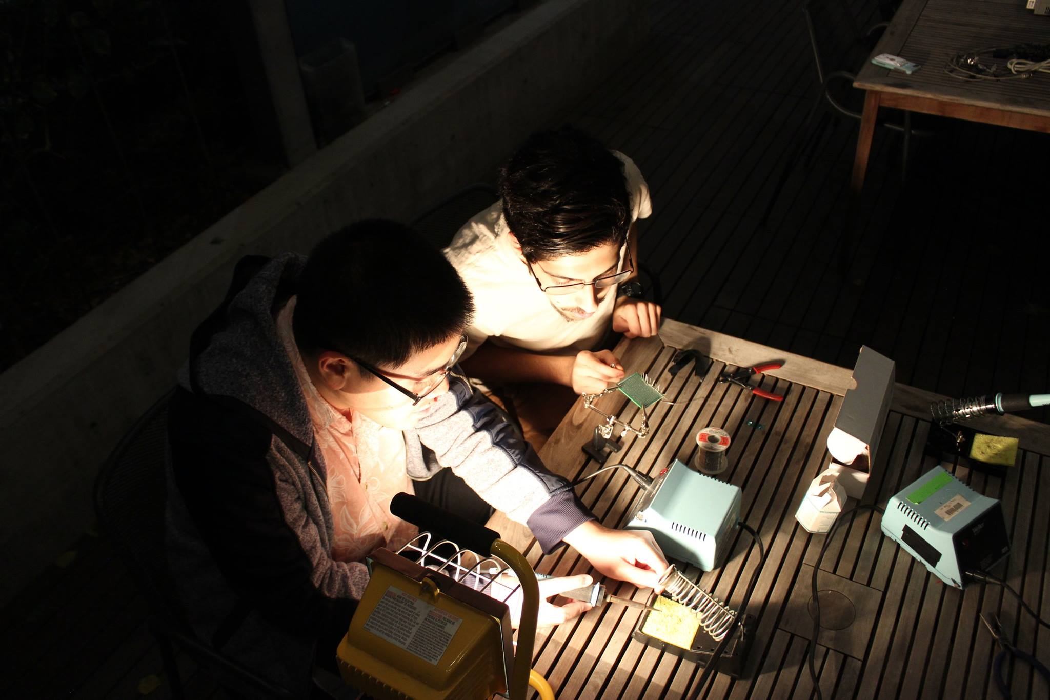 Two students soldering in the outdoor classroom, in the dark