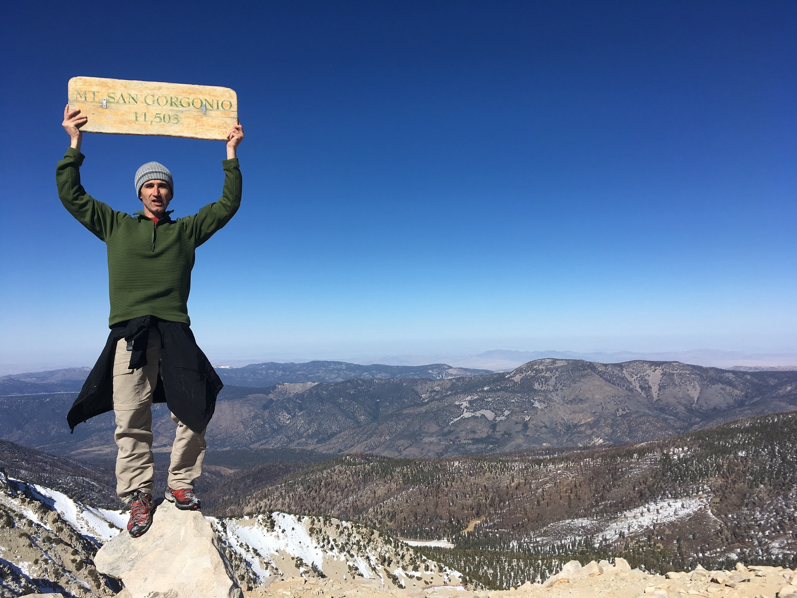 Professor Zorman at the top of Mt. San Gorgonio, proudly holding up a sign with its elevation: 11,503ft
