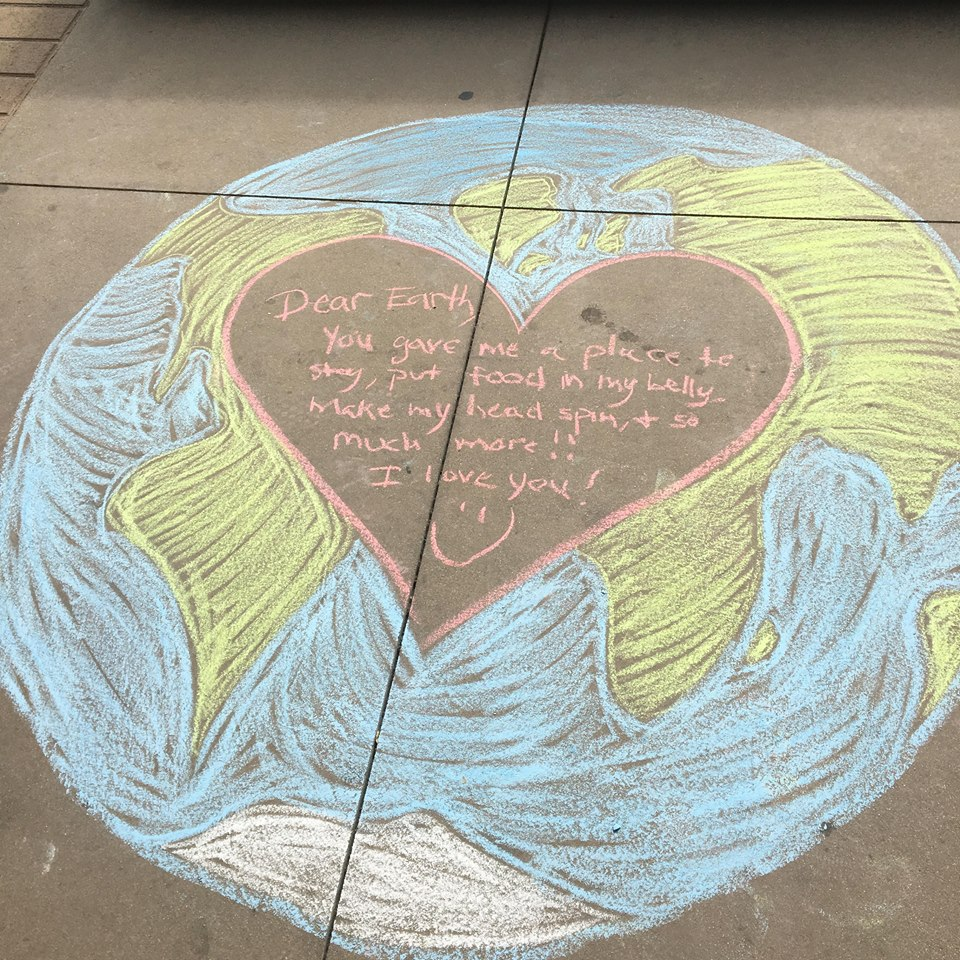 A chalk drawing of the earth on the sidewalk, with a heart in the center.