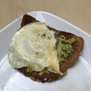 toasted oat wheat bread with mashed avocado and a medium fried egg