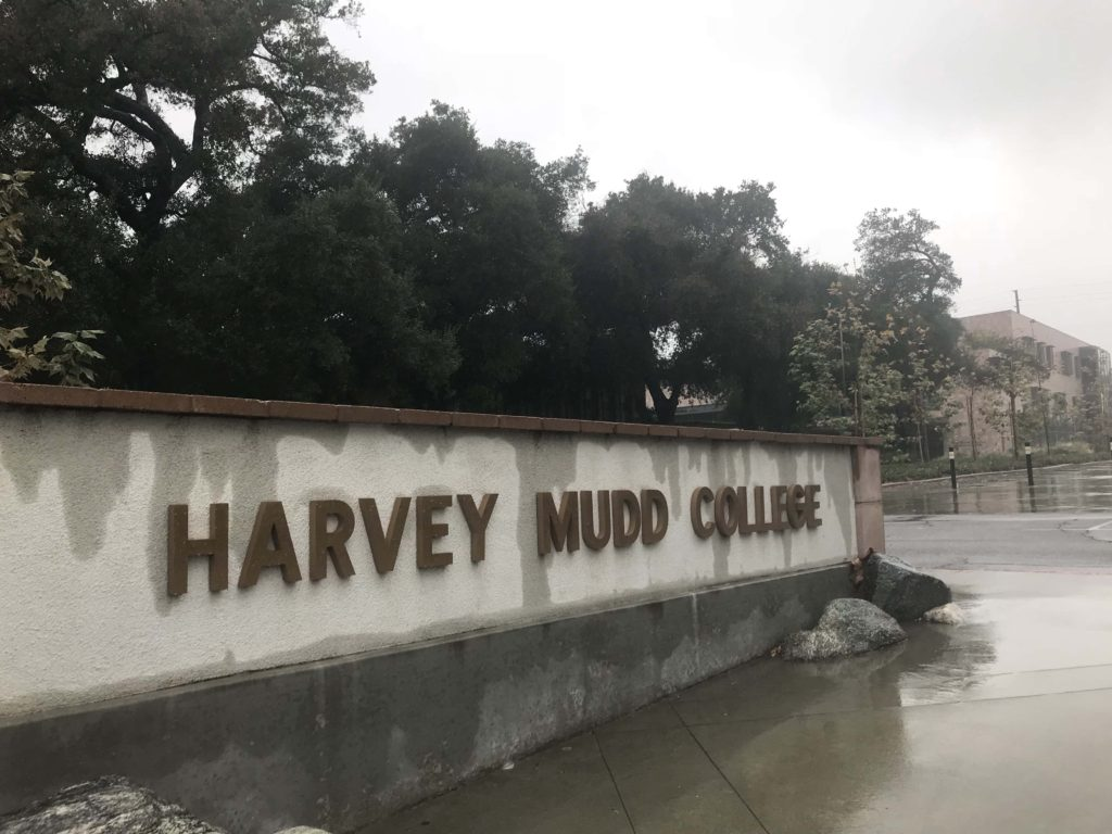 A dramatically angled shot of the Harvey Mudd College sign, streaked with rain.