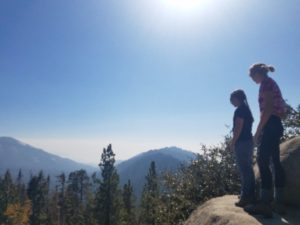 Two students stand on a boulder as they look off into the tree covered canyon. In the background, the mountains are outlined and show off various shades of blue and green. Above, the sky is completely clear allowing for the solar rays to penetrate all parts of the wilderness.