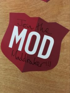 "A red sticker with white text spelling out ""MOD"". Around that are the words ""Join the Muddraker!!!"""