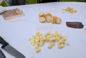 A piece of butcher paper with baguette slices in the center, and piles of small cheese cubes and slices of cured meats