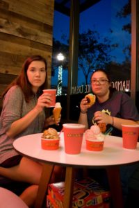 Two girls sit at a table and stare into the camera, surrounded by three cups of coffee and four types of ice cream.