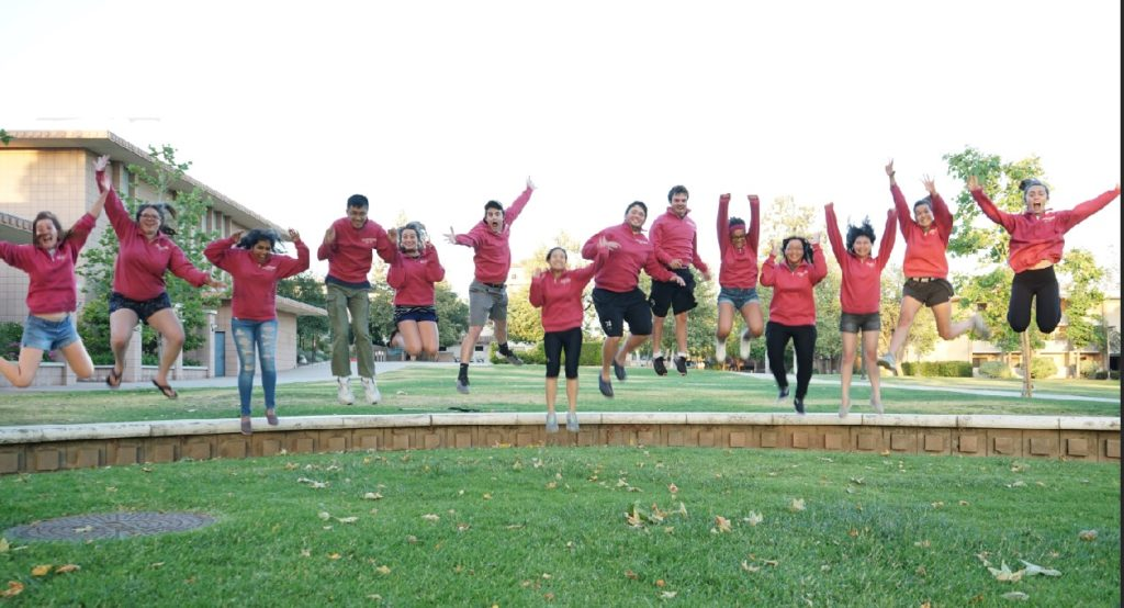 Fourteen college students on a lawn wearing identical red sweatshirts jump in the air