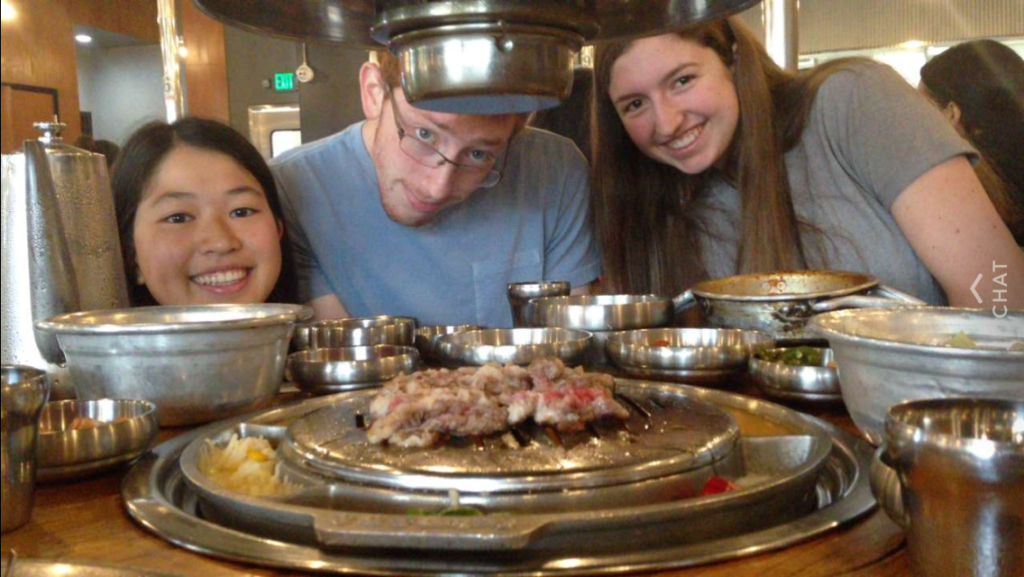 Three students with many metal bowls and meat on a Korean barbecue grill.