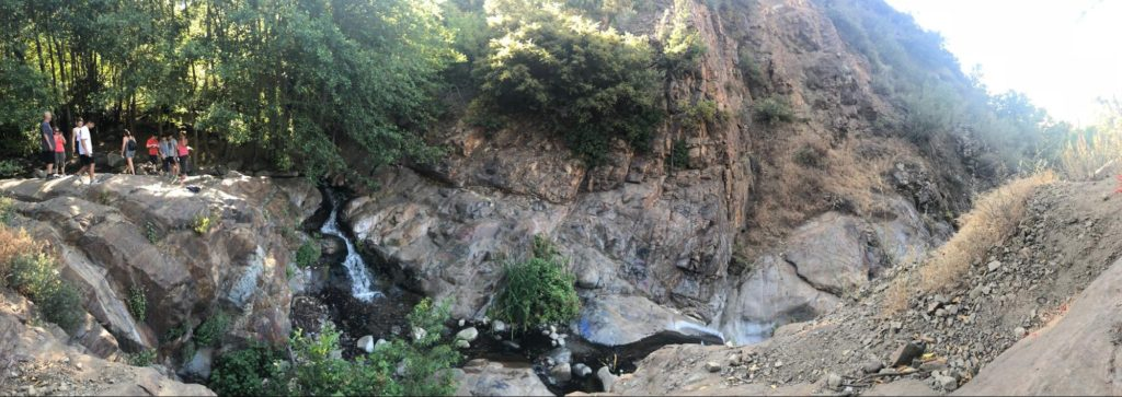 A panorama of a small waterfall and a rocky hillside.