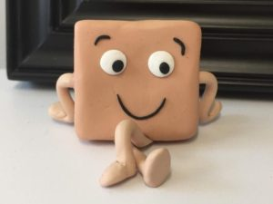 An anthropomorphic square prism smiles and crosses its legs, appearing to be sitting down