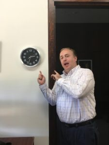 A photograph of Paul Hardister pointing to a clock.