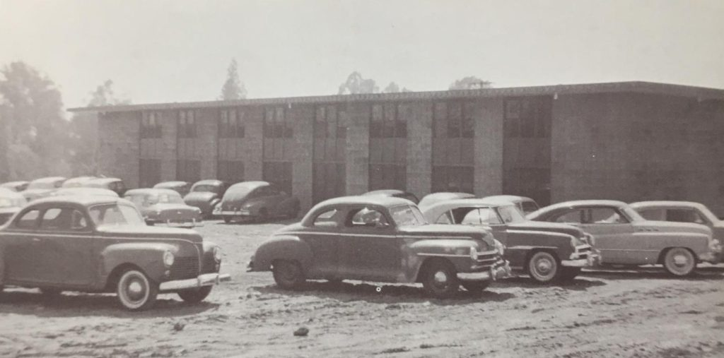 Cars parked on a dirt lot in front of a concrete building