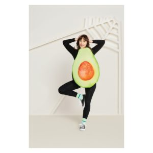 A woman poses in an avocado costume. Her torso has half an avocado on it.
