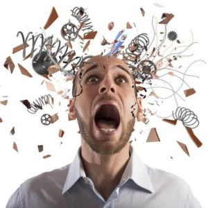 Picture depicts a person screaming, wide-eyed, while debris is flying all around their head. They look very stressed.