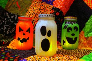 A picture of three jars, which have been decorated to look like a carved pumpkin, a cartoon ghost, and a cartoon Frankenstein.