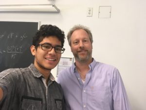 Mason Acevedo (the writer) and Professor Johnson in a selfie together. Both are standing in a classroom, with slightly awkward and forced smiles.
