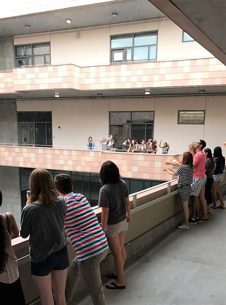 A group of students standing on the balcony of an academic building staring at the sky where rain is falling.
