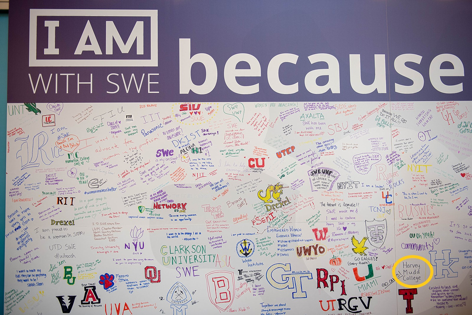 "A board with a bunch of different colleges written under a large prompt ""I am with SWE because"""