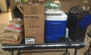 Picture shows a grill with lots of items stacked on it, including a large tray of fruit, a cooler for meat patties, a box of chips and plates, and a cooler/dispenser for lemonade.