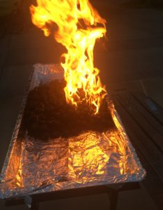 The picture shows the same mound of coals on fire, except in this picture, the fire was doused with lighter fluid just a few seconds ago, so the fire is particularly bright and impressive.